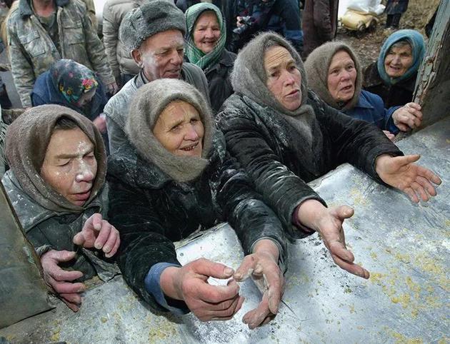 2005年,居住在切尔诺贝利禁区内的妇女正在领食物。  来源:Ivan Chernichkin/Reuters